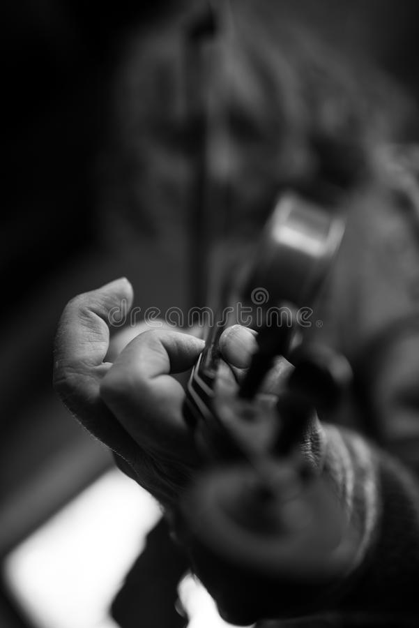 Greyscale image of elderly male musician with dirty nails playing a violin stock images