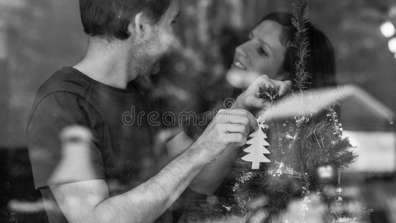 Greyscale image of a loving young couple decorating Christmas tr stock photo