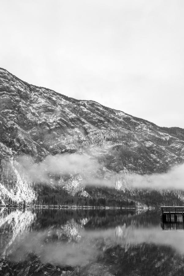 Old wooden pier on calm winter lake with mountain in background and mist above the water stock photography