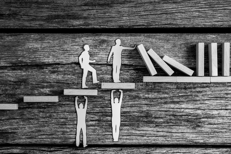 Greyscale image of small paper people holding up falling dominos while standing on wooden steps stock images