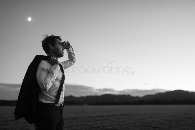 Greyscale Image of a Young Businessman Standing at the Field stock photography