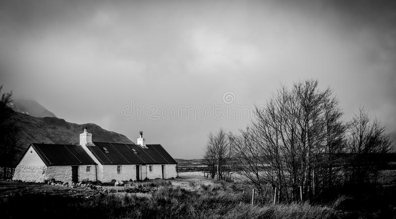Greyscale Photo of House Within Mountain Range royalty free stock photos