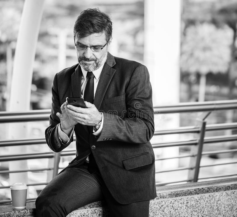 Greyscale Photo Of Man Wearing Suit Jacket And Eyeglasses Holding Smartphone royalty free stock photography