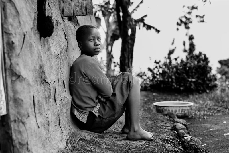 Greyscale Photography of Boy Sitting Behind Wall royalty free stock photo