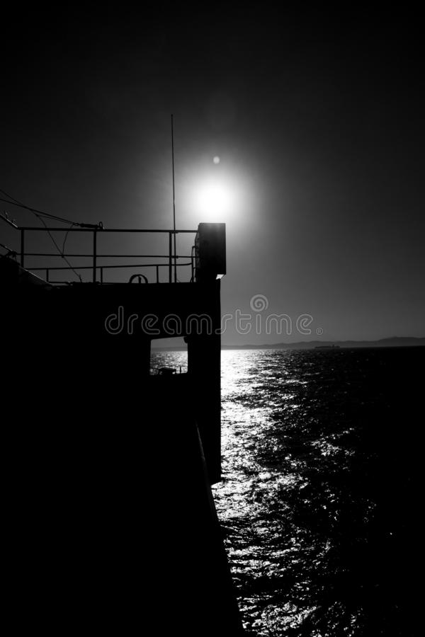 Greyscale of a sea with a ship on it under the sunlight during daytime. A greyscale of a sea with a ship on it under the sunlight during daytime royalty free stock image