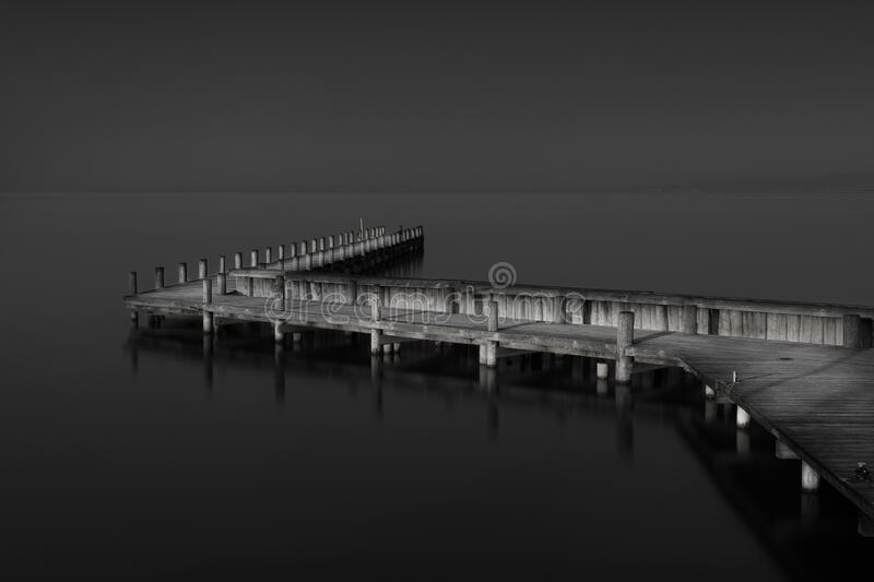 Greyscale shot of a wooden pier near the sea during daytime. A greyscale shot of a wooden pier near the sea during daytime royalty free stock photography
