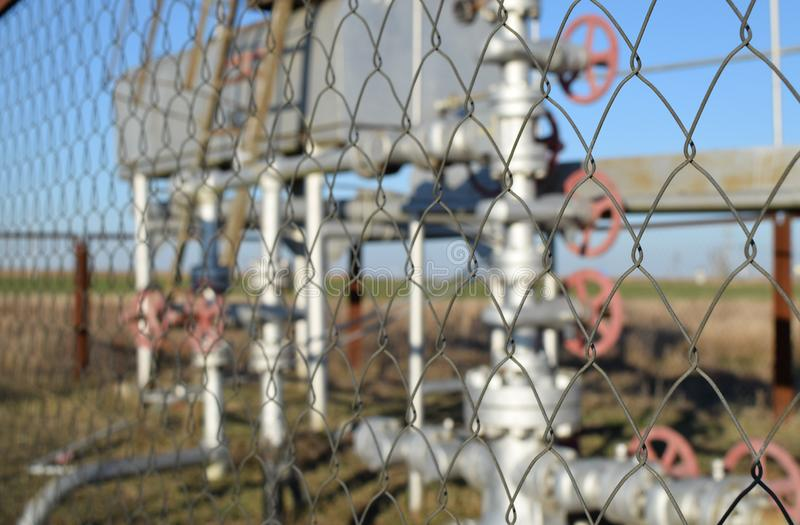 Grid the chain-link near an oil well. Shutoff valves and service equipment stock images