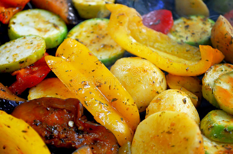 On the grid grill are fried vegetables. Potatoes, tomatoes, peppers, eggplants, cucumbers, zucchini, carrots and seasonings with o stock image
