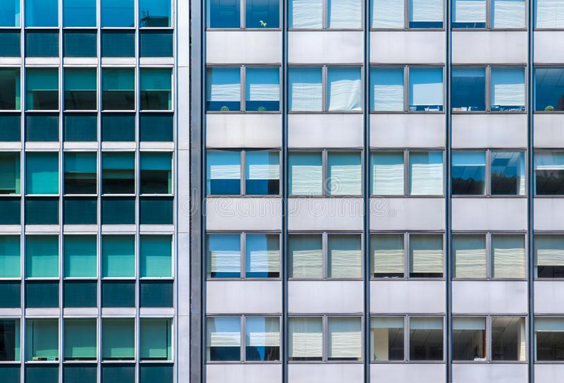 A grid of office windows in two modern glass and steel buildings side by side with contrasting colors. Lines of office windows in two modern glass and steel royalty free stock photos