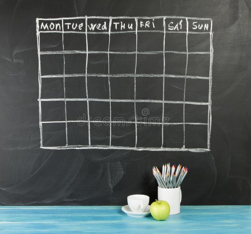 Grid timetable schedule on black chalkboard background. royalty free stock photos