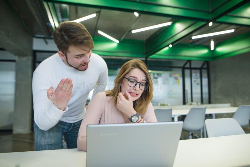 grida dell'uomo ad una bella ragazza che si siede alla tavola e che lavora al computer La situazione nell'ufficio immagine stock libera da diritti