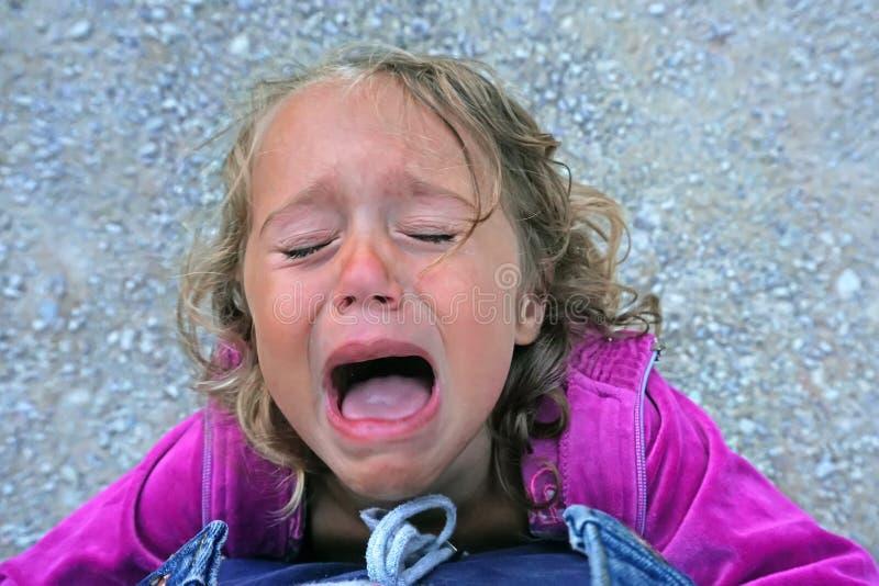 Grida di 3-4 anni della ragazza perché è rimproverata tramite sua madre fotografia stock