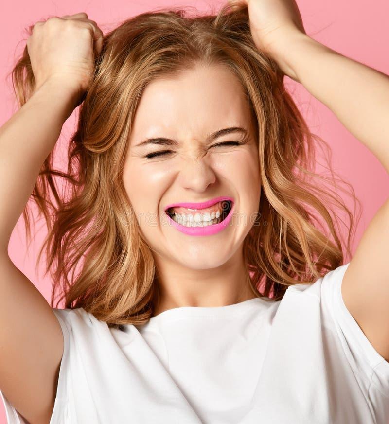 Gridare di grido della donna emozionale urlando il ritratto del primo piano su tirata rosa del fondo che strappa capelli capi fotografia stock