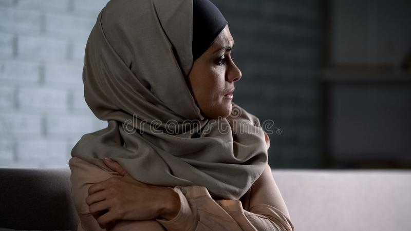 Gridare la mano dolorosa della tenuta femminile musulmana, soffrente dalla violenza del marito fotografie stock libere da diritti