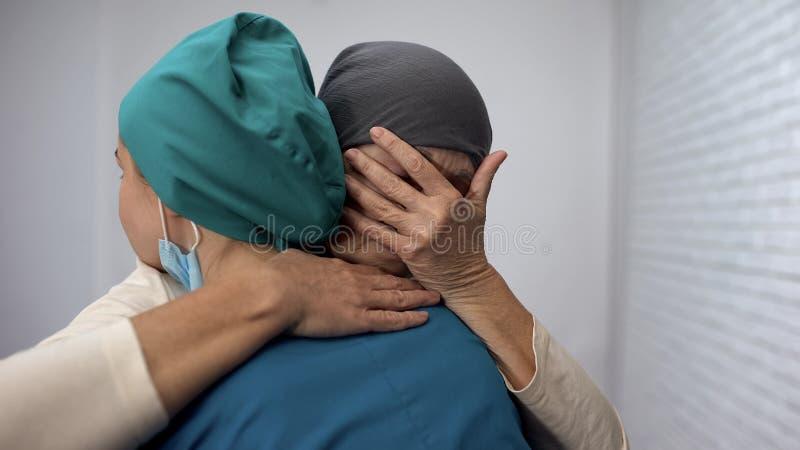 Gridare oncologo abbracciante femminile malato, nessuna speranza, notizie deludenti, sarcoma fotografie stock