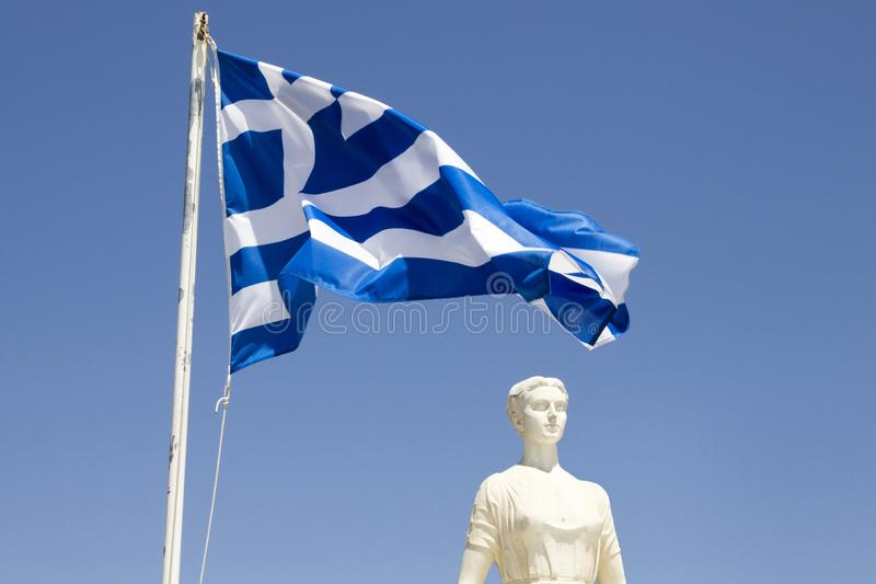 Griechische Flagge mit weißer Marmorstatue in Skiathos-Hafen, Skiathos-Stadt, Griechenland am 18. August lizenzfreie stockfotografie