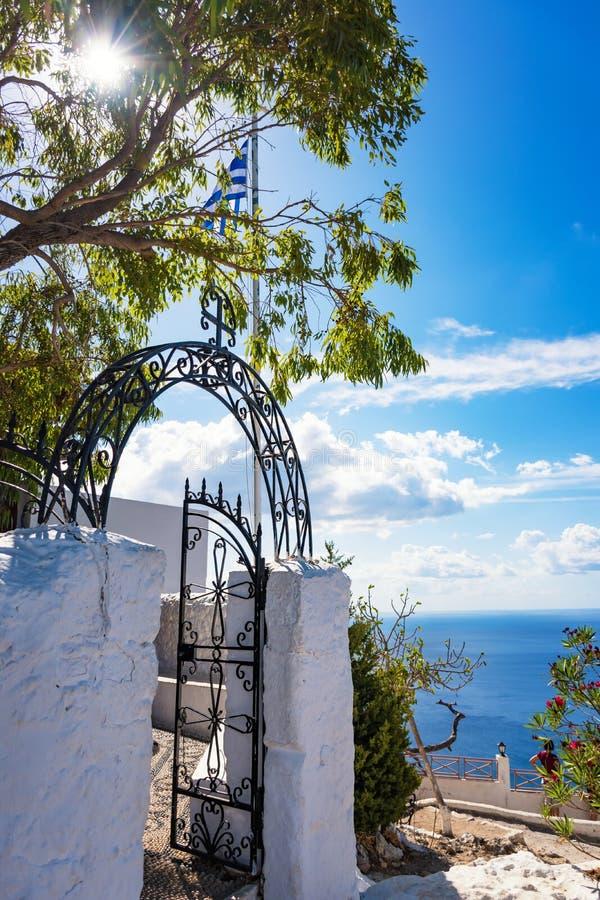 Griechische Flagge und Eingang zu Tsambika-Kloster, RHODOS, GRIECHENLAND lizenzfreie stockbilder