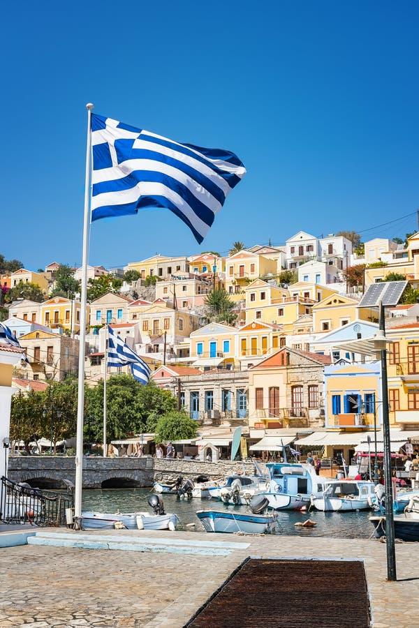Griechische Flaggen, Boote und bunte neoklassische Häuser in der Hafenstadt von Insel Symi Symi, Griechenland lizenzfreies stockbild
