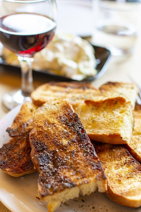 Griechische Nahrung, gebratenes Brot, Rotwein und tzatziki Soße gemacht vom gesalzenen belasteten Jogurt gemischt mit Gurken, Kno lizenzfreies stockfoto