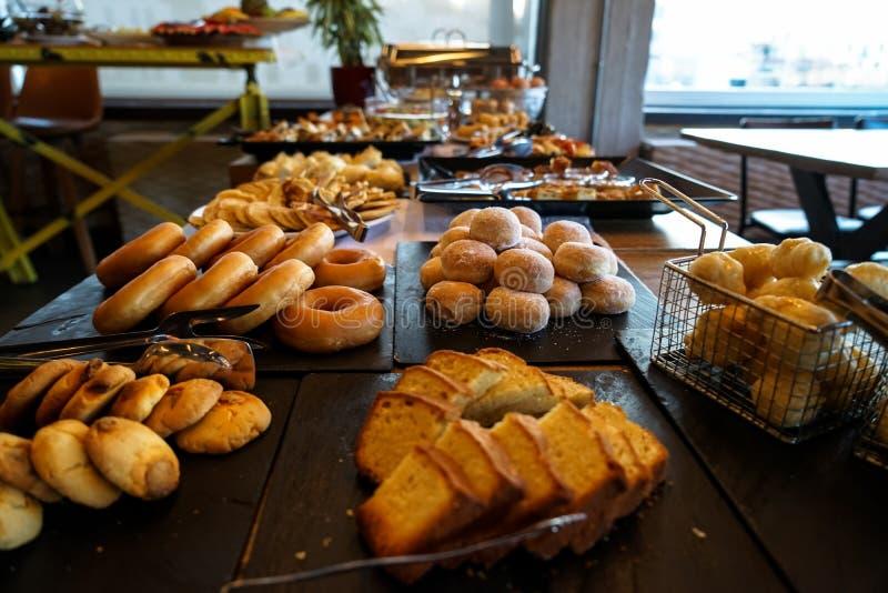 Griechischer Frühstücksbuffettisch voll mit Vielzahl des Gebäcks, Brötchen, Pfannkuchen, Schaumgummiringe, Butterkuchen, Pizza, T stockbilder