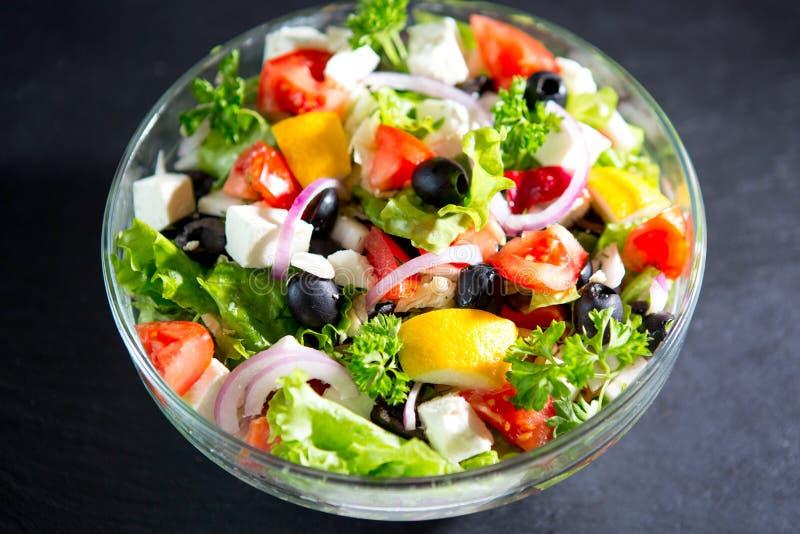 Griechischer Salat in einer Schüssel auf schwarzer Steintabelle, Draufsicht stockbild