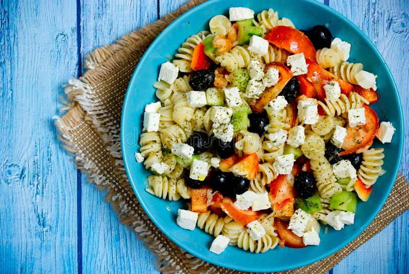 Griechischer Salat mit Frischgemüse, Feta, Teigwaren und schwarzen Oliven lizenzfreies stockbild