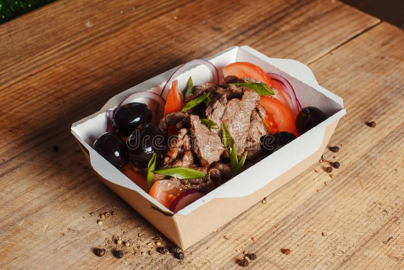 Griechischer Salat mit Kalbfleisch in einem Kasten stockfoto