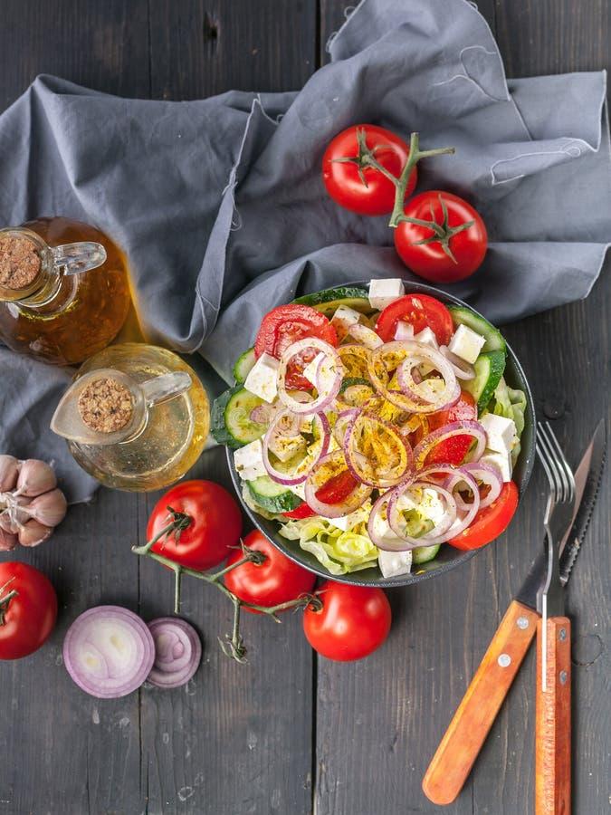 Griechischer Salat mit Olivenöl und Gewürzen Zwiebel, Knoblauch, Gabel und Löffel, graue Serviette auf einem dunklen Holztisch Be lizenzfreie stockbilder