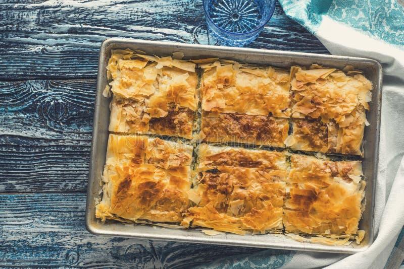 Griechisches Torte spanakopita in der Metallwanne auf der blauen Draufsicht des Holztischs stockfotos