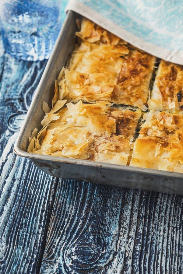 Griechisches Torte spanakopita in der Metallwanne auf der blauen Holztischvertikale lizenzfreies stockfoto