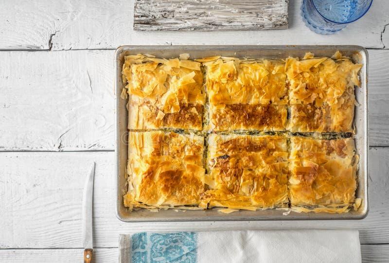 Griechisches Torte spanakopita in der Metallwanne mit Draufsicht des Essgeschirrs lizenzfreie stockfotos