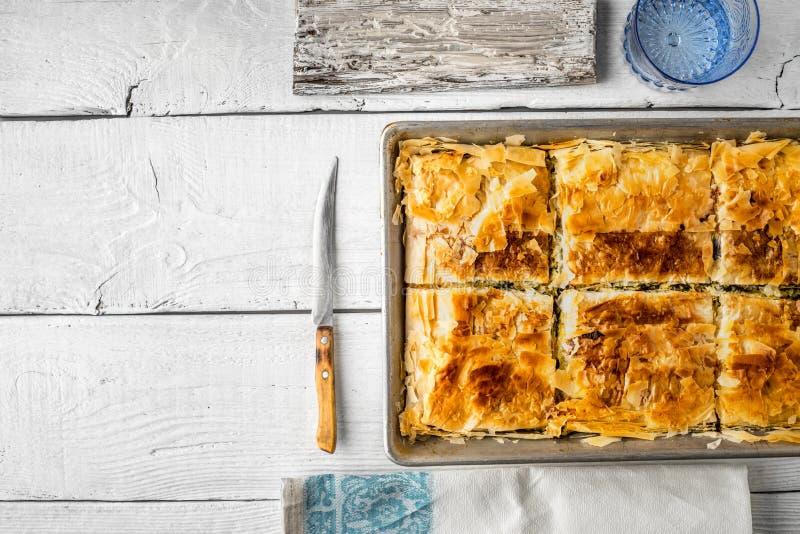 Griechisches Torte spanakopita in der Metallwanne mit Essgeschirr lizenzfreie stockfotografie