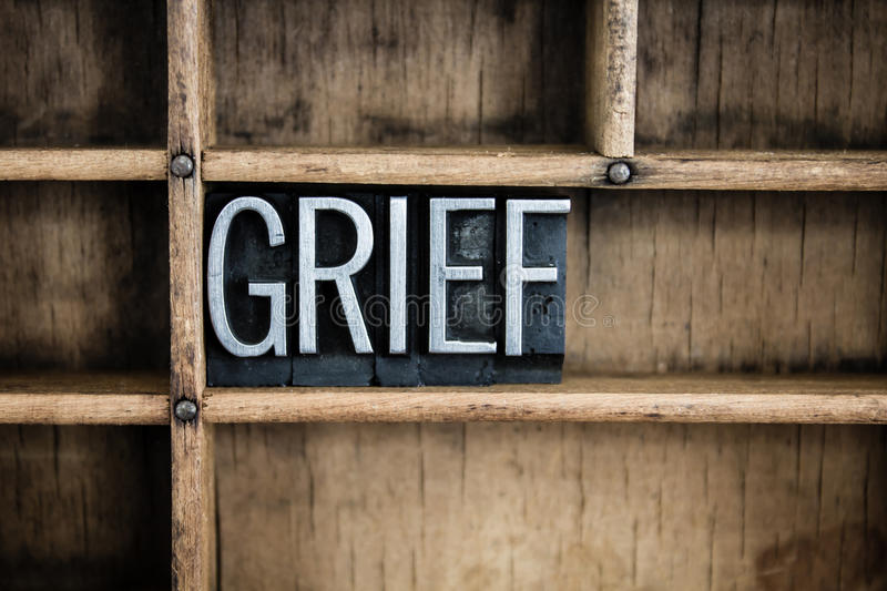 Grief Concept Metal Letterpress Word in Drawer. The word GRIEF written in vintage metal letterpress type in a wooden drawer with dividers royalty free stock images