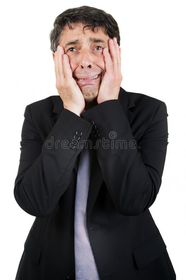 Griefstricken businessman. Holding his face in his hands as he cries to himself with a woebegone expression, isolated on white royalty free stock images