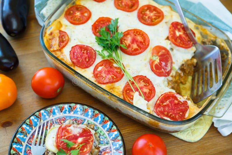 Griego Moussaka con las berenjenas, patatas, carne picadita, tomates, fotografía de archivo