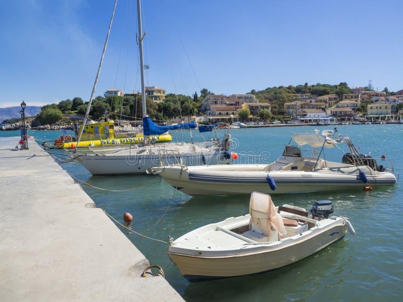 Griekenland, Korfu, Kassiopi 28 september, 2018: Kade en haven met binnen vissersboten en jacht in Kassiopi, toeristendorp royalty-vrije stock fotografie