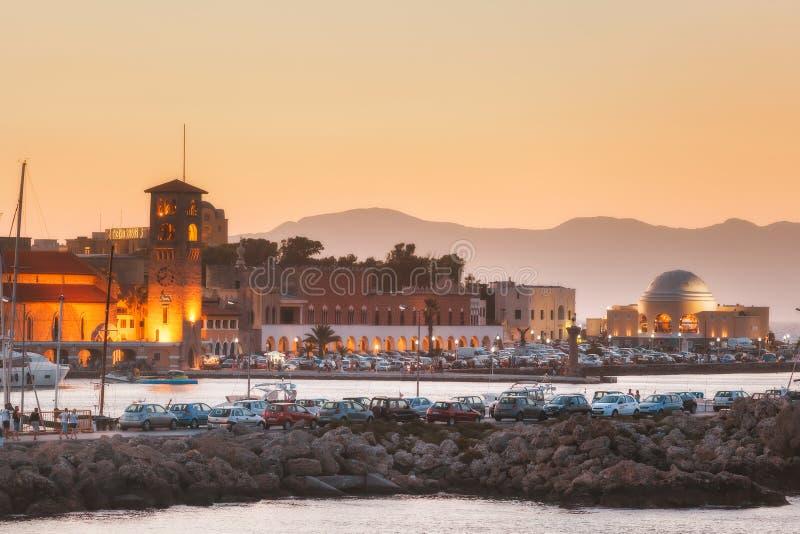 Griekenland, Rhodos - Juli 13 de dijk en de haven van Mandraki bij zonsondergang op 13 Juli, 2014 in Rhodos, Griekenland stock foto's