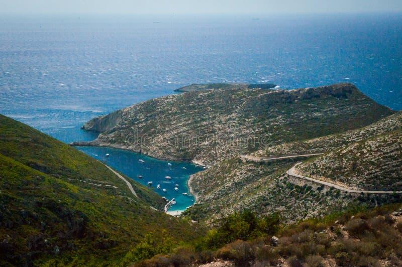 Griekenland, Zakynthos, Augustus 2016 Rotsen, holen en blauw water Mening van observatiepunt aan panorama van eiland, baai en weg royalty-vrije stock afbeelding