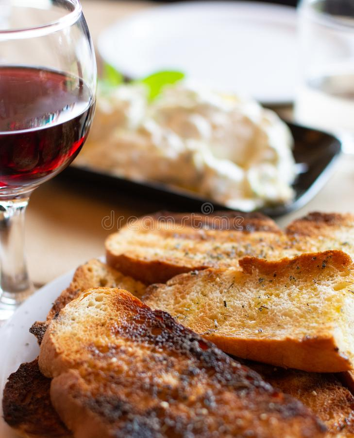Grieks voedsel, geroosterd brood met olijfolie en kruiden, rode wijn en tzatzikisaus stock afbeeldingen