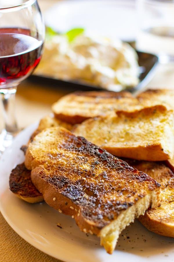 Grieks voedsel, geroosterd brood met olijfolie en kruiden, rode wijn en tzatzikisaus royalty-vrije stock foto's