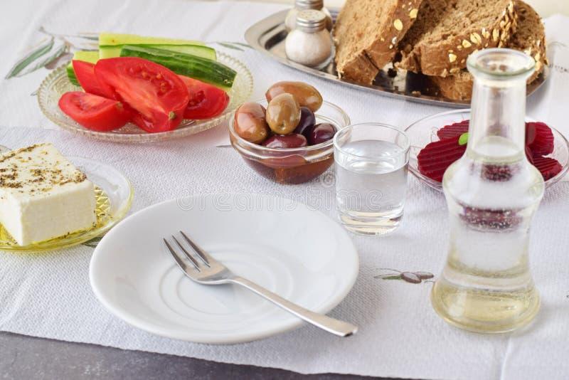 Grieks voedsel, mezedes Kruiken met olijfolie en wijnstokazijn, olijven, feta, tzatziki, donker brood, raki, verse bieten, stock foto's