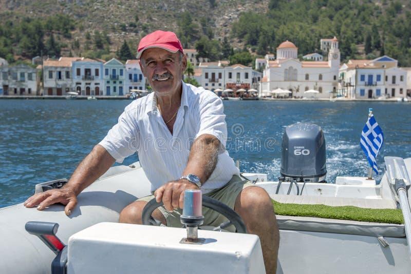 Griekse boot kapiteinsGeorge hoofden uit de haven op het Griekse Eiland Kastellorizo stock fotografie