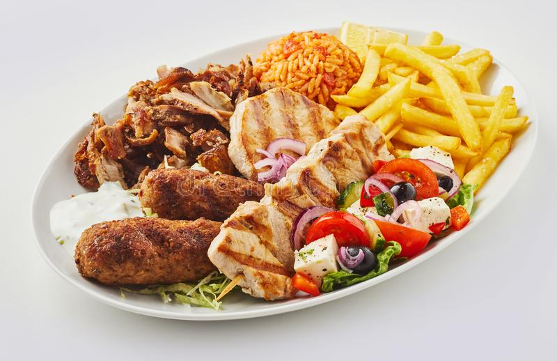 Griekse gemengde grillschotel met salade en spaanders stock afbeelding