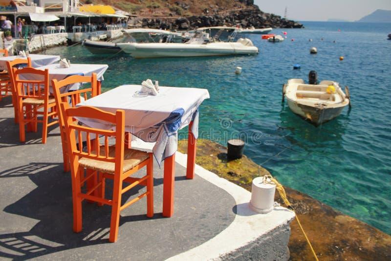 Griekse herberg met oranje houten stoelen door de overzeese kust, Griekenland, stock foto