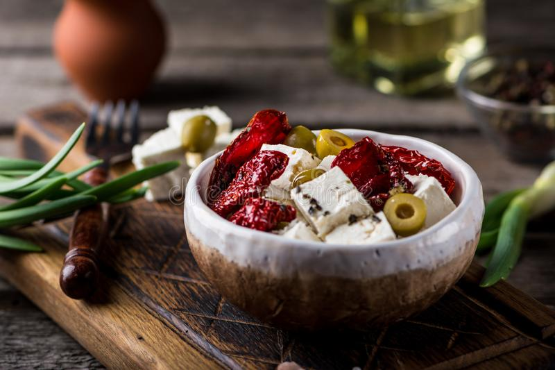 Griekse kaas feta met kruiden en olijven, in de zon gedroogde tomaten Bulgaarse kaas Feta in olie Oloveolie Selectieve nadruk royalty-vrije stock foto