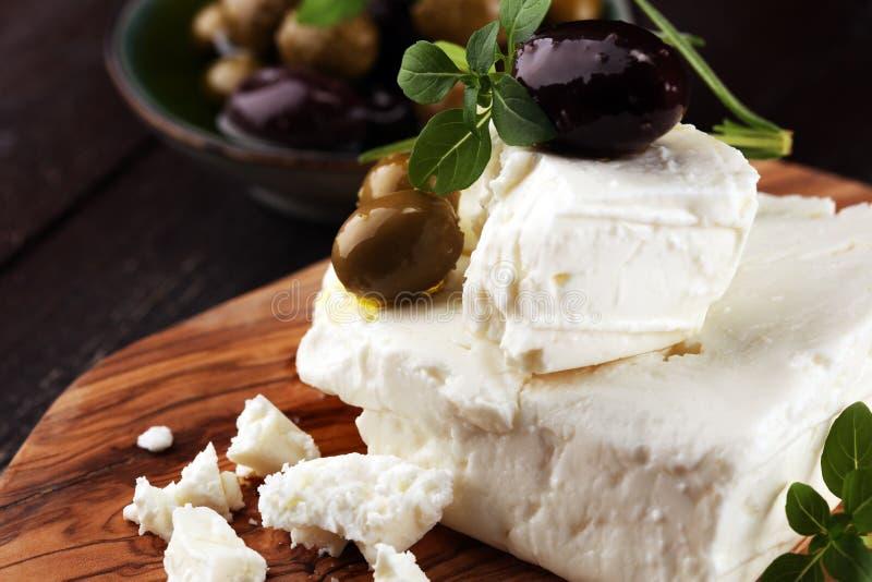 Griekse kaas feta met kruiden en olijven op rustieke lijst royalty-vrije stock foto