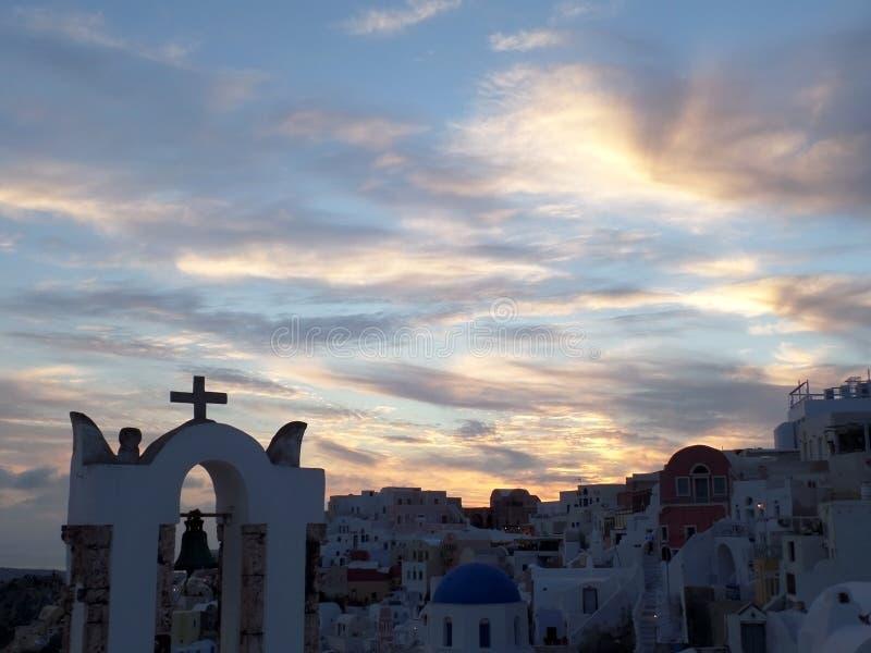 Griekse kerk tegen het overweldigen van zonsonderganghemel bij Oia dorp, Santorini-eiland stock afbeelding