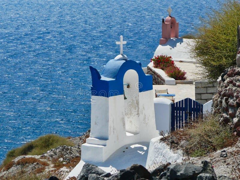 Griekse Orthodoxe Kerken die het Egeïsche Overzees, Oia, Santorini, Griekenland overzien royalty-vrije stock afbeelding