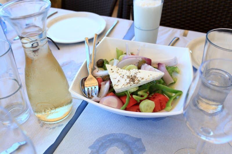 Griekse salade en witte wijn stock fotografie