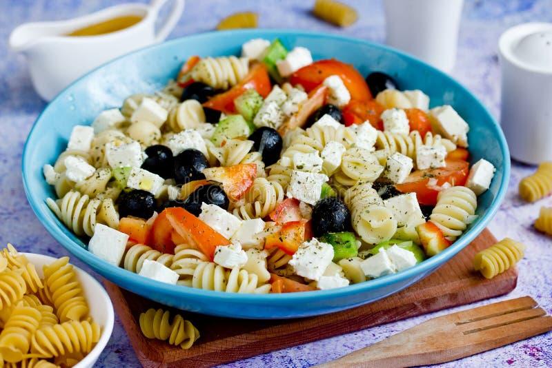Griekse salade met verse groenten, feta-kaas, deegwaren en zwarte olijven royalty-vrije stock foto's